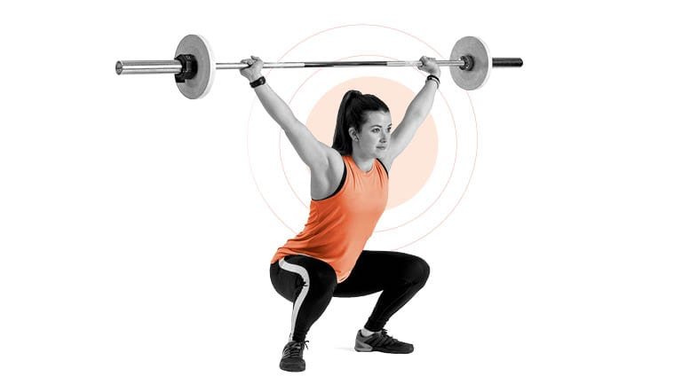 a woman performs an overhead squat